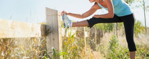 woman stretching next to a fence
