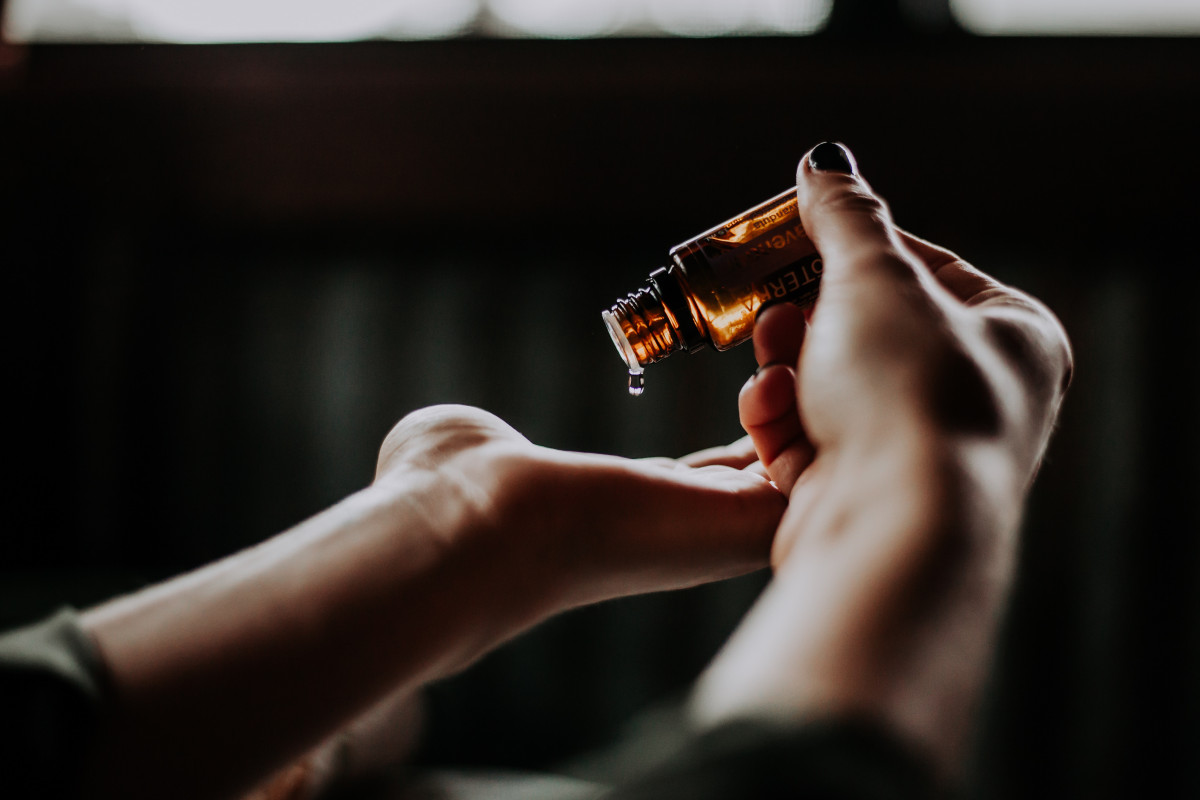 person squeezing drops of essential oil from a bottle