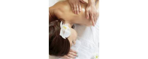image of woman with flower in hair, getting a massage
