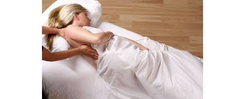 image of expecting mother getting massage on table under sheet